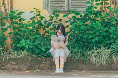 woman wearing white dress reading book